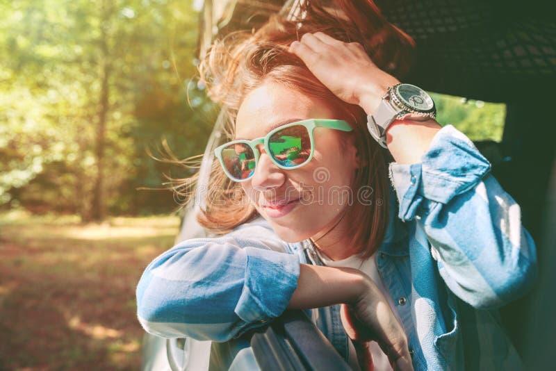 Gelukkige jonge vrouw die door de vensterauto kijken stock foto