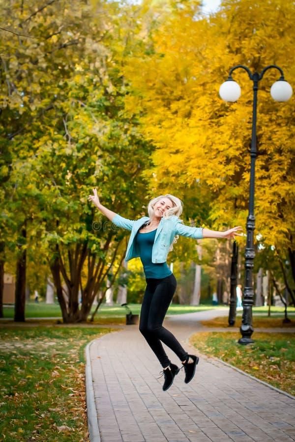 Gelukkige jonge vrouw die en van het leven in de herfstpark springen genieten royalty-vrije stock fotografie