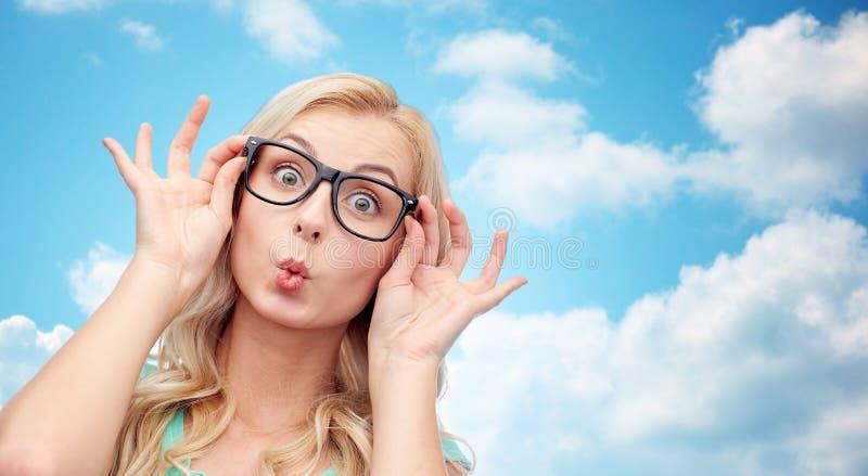 Gelukkige jonge vrouw die in glazen vissengezicht maken stock afbeelding