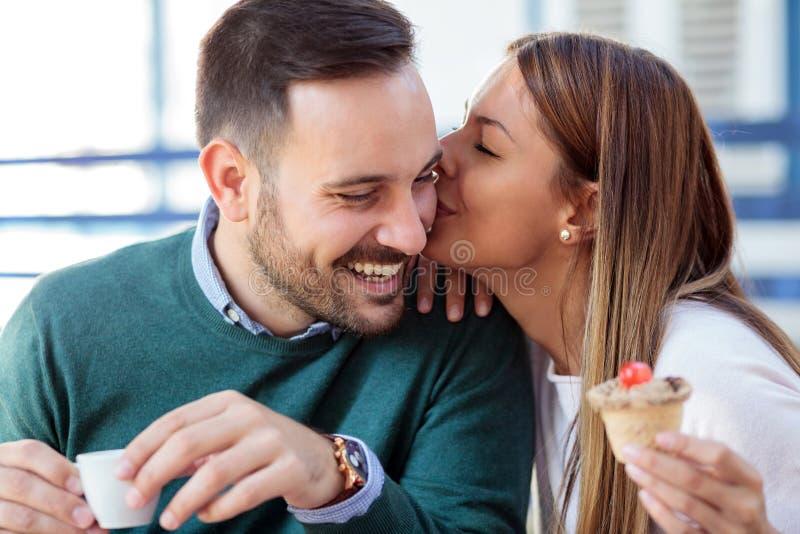 Gelukkige jonge vrouw die haar echtgenoot of vriend op de wang kussen Romantische datum in een koffie royalty-vrije stock foto's