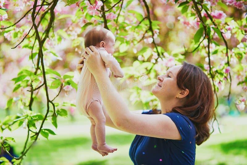 Gelukkige jonge vrouw die haar houden weinig babymeisje stock foto's