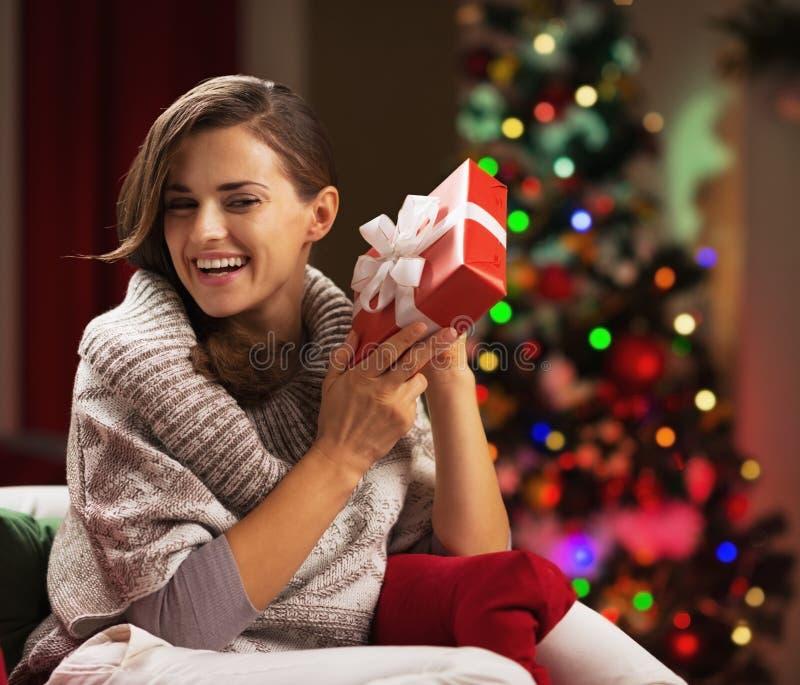Gelukkige jonge vrouw die huidige doos schudden dichtbij Kerstmisboom stock afbeeldingen