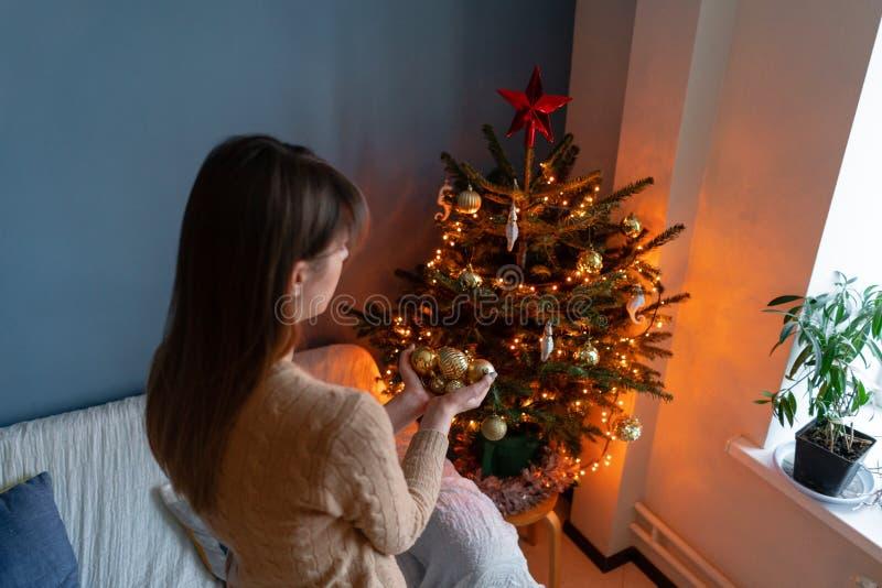 Gelukkige jonge vrouw die Kerstboom thuis verfraaien De wintervakantie in een huisbinnenland Gouden en witte Kerstmis royalty-vrije stock afbeeldingen