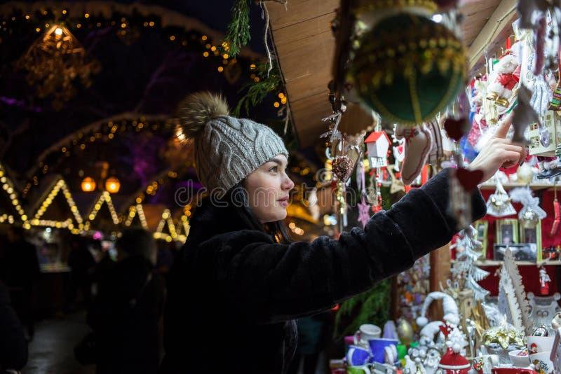 Gelukkige jonge vrouw die Kerstmisdecoratie kiezen bij markt stock foto