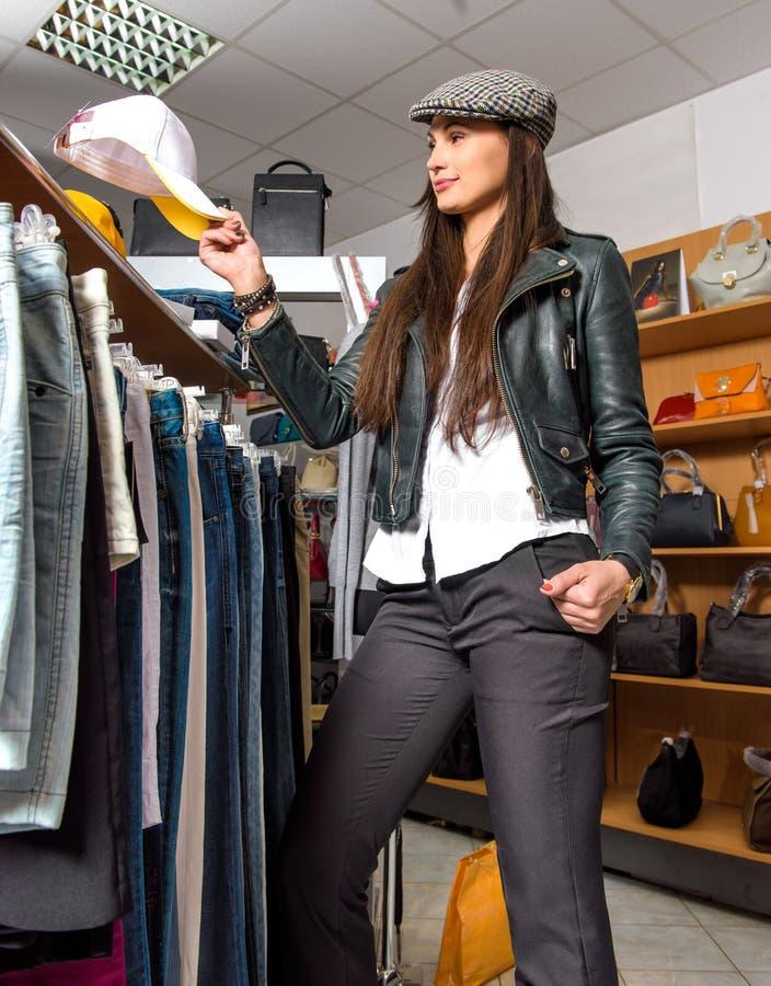 Gelukkige jonge vrouw die kleren kiest stock foto's