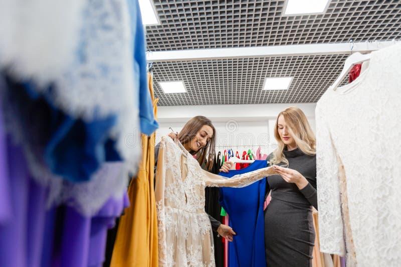 Gelukkige jonge vrouw die kleren in wandelgalerij kiezen of opslag kleden stock afbeelding