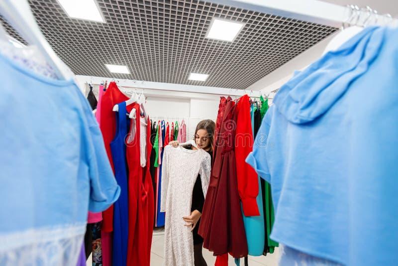 Gelukkige jonge vrouw die kleren in wandelgalerij kiezen of opslag kleden royalty-vrije stock foto's