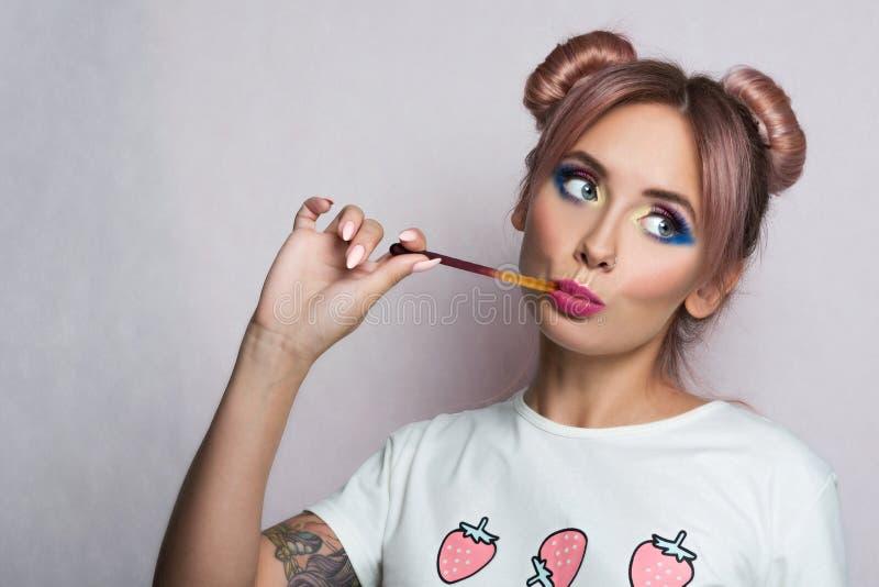 Gelukkige jonge vrouw die kleverig suikergoed eten stock afbeelding