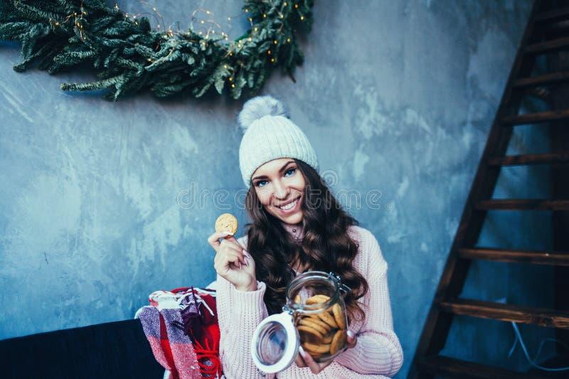 Gelukkige jonge vrouw die koekje thuis eten royalty-vrije stock foto's