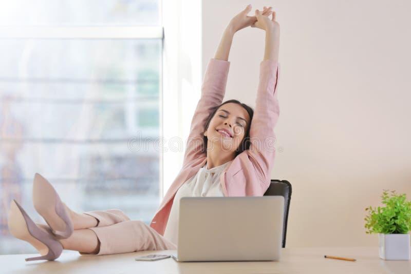 Gelukkige jonge vrouw die korte rust hebben op het werk stock fotografie