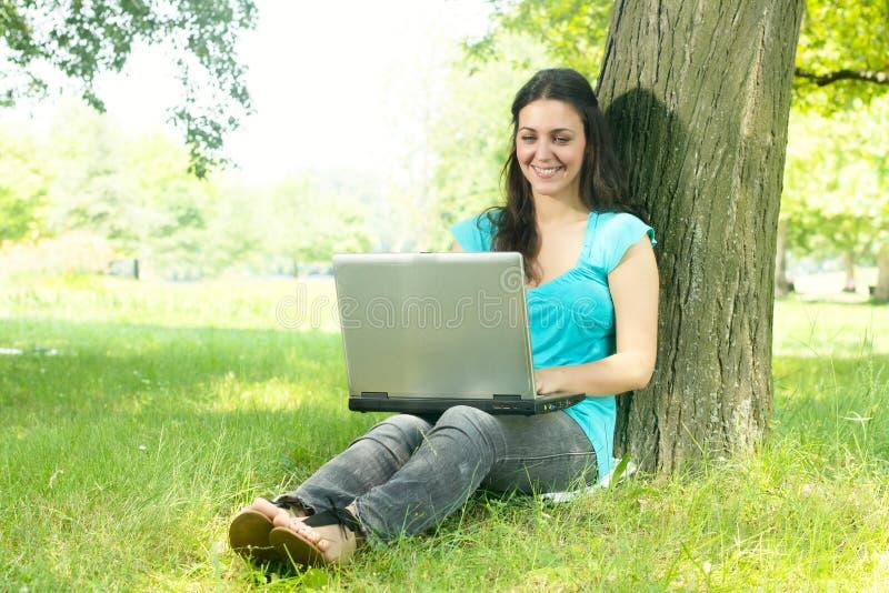 Gelukkige jonge vrouw die laptop in openlucht met behulp van royalty-vrije stock foto's