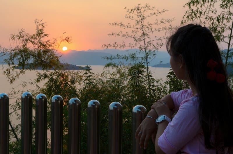Gelukkige jonge vrouw die lettend op de zonsondergang over het meer bevinden zich royalty-vrije stock afbeelding