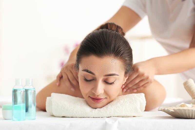 Gelukkige jonge vrouw die massage in kuuroordsalon hebben stock afbeelding