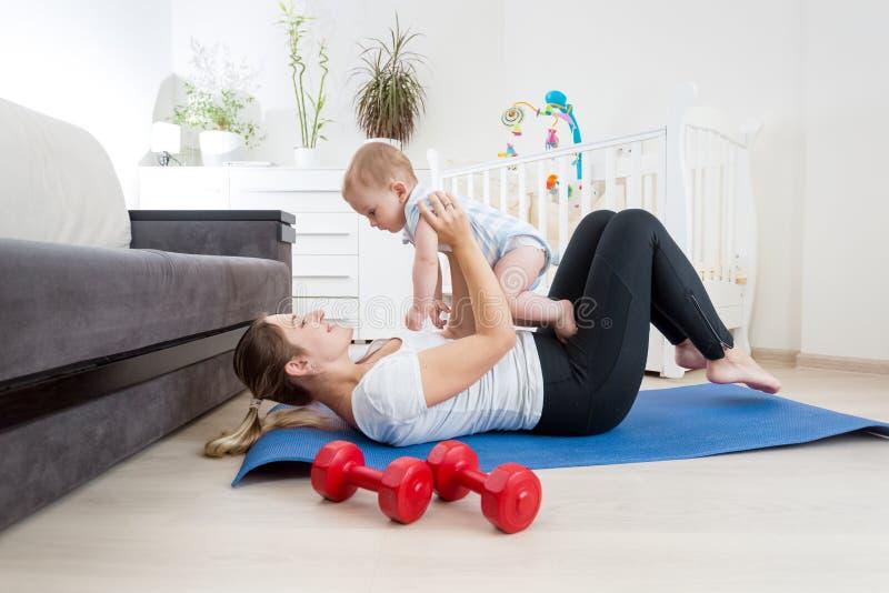 Gelukkige jonge vrouw die met haar babyjongen op vloer bij woonkamer uitoefenen stock afbeeldingen