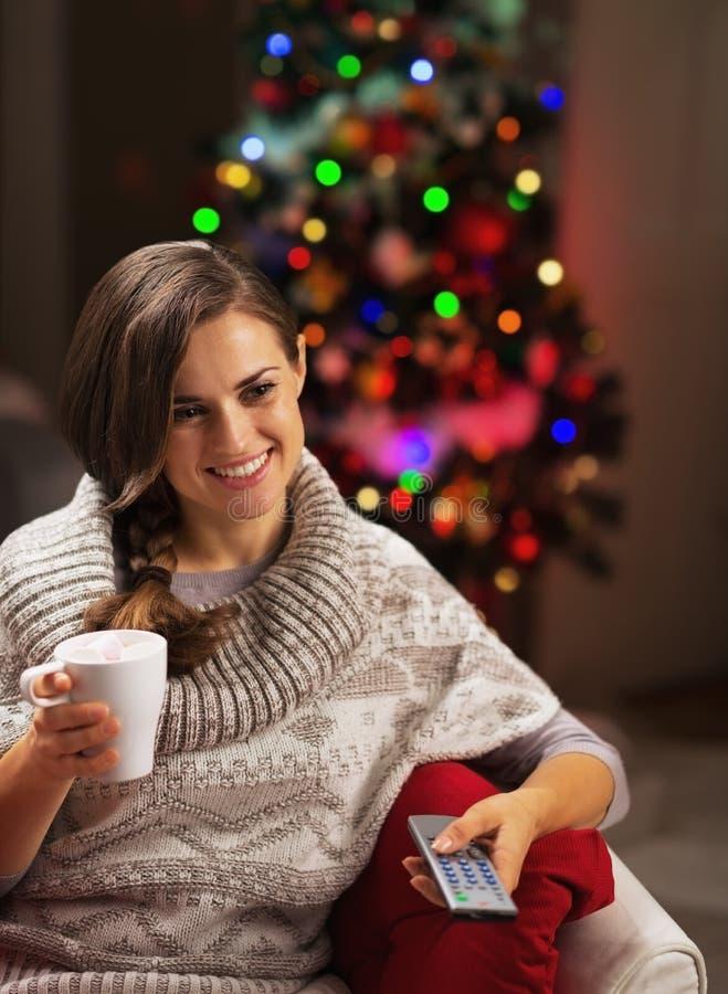 Gelukkige jonge vrouw die met kop van hete chocolade op TV letten stock foto's