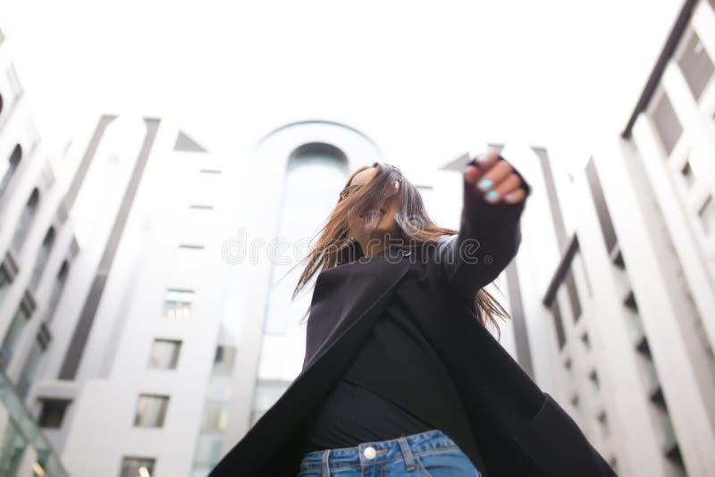 Gelukkige jonge vrouw die met lang haar in glazen bij de stad lopen royalty-vrije stock fotografie