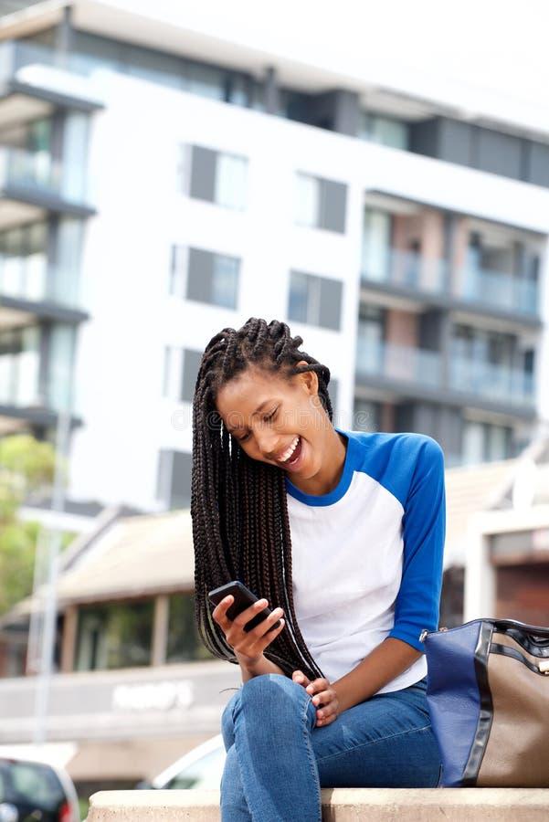Gelukkige jonge vrouw die mobiele telefoon bekijken en buiten in de stad glimlachen stock fotografie