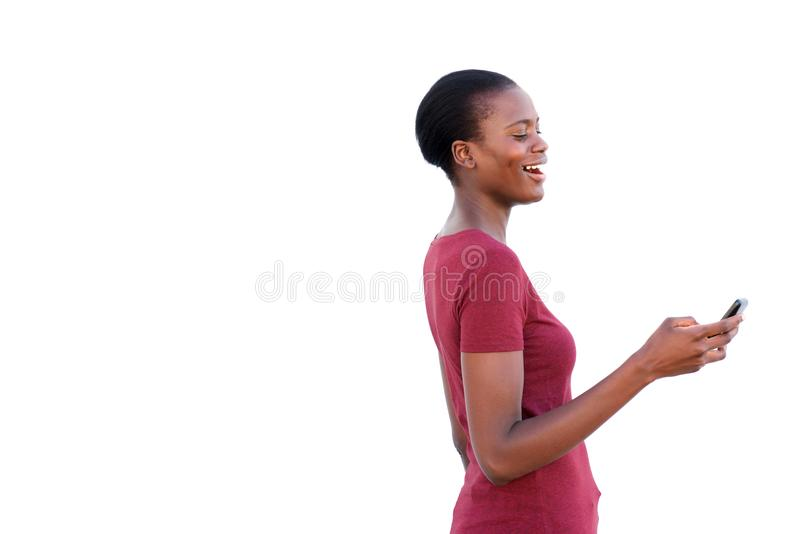 Gelukkige jonge vrouw die mobiele telefoon bekijken en op witte achtergrond lachen stock foto's