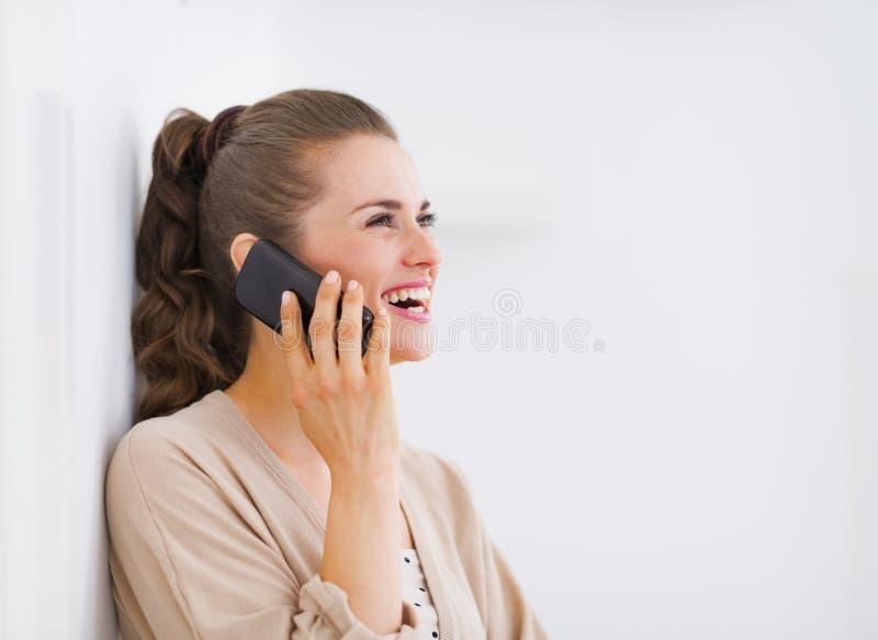 Gelukkige jonge vrouw die mobiele telefoon spreken en op exemplaarruimte kijken stock fotografie