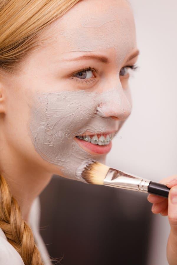 Gelukkige jonge vrouw die moddermasker op gezicht toepassen stock foto