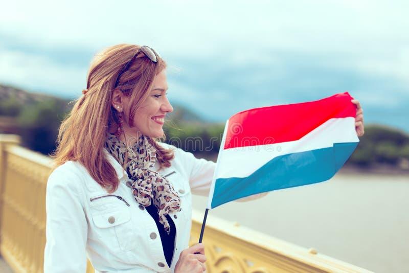 Gelukkige jonge vrouw die Nederlandse vlag op brug uitrekken stock foto's