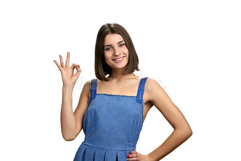 Gelukkige jonge vrouw die o.k. teken met vingers tonen stock fotografie