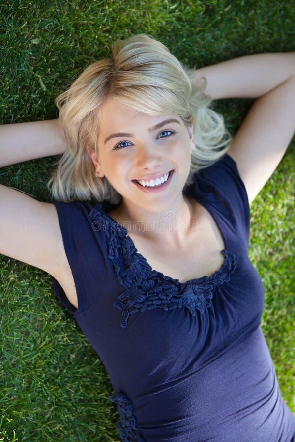 Gelukkige jonge vrouw die op gras liggen royalty-vrije stock fotografie