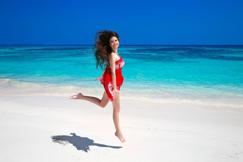 Gelukkige jonge vrouw die op het overzees, donkerbruin glimlachend meisje in r springen royalty-vrije stock afbeelding