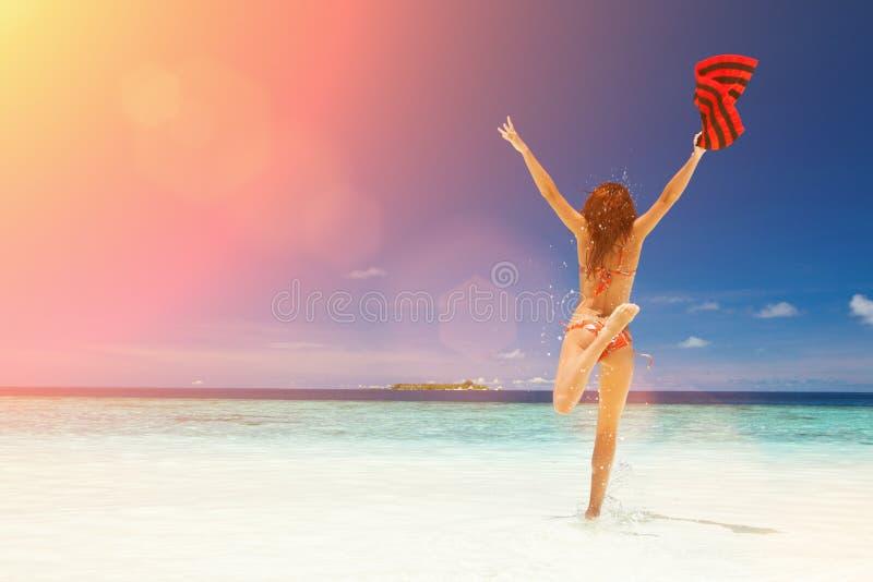 Gelukkige jonge vrouw die op het strand springt Gelukkige Levensstijl stock foto