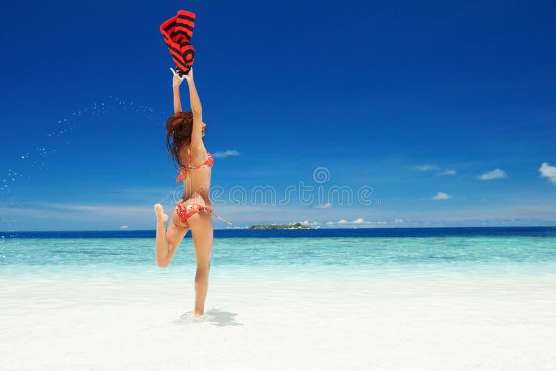 Gelukkige jonge vrouw die op het strand springt Gelukkige Levensstijl Wit zand, blauwe hemel en kristaloverzees van tropisch stra stock afbeelding