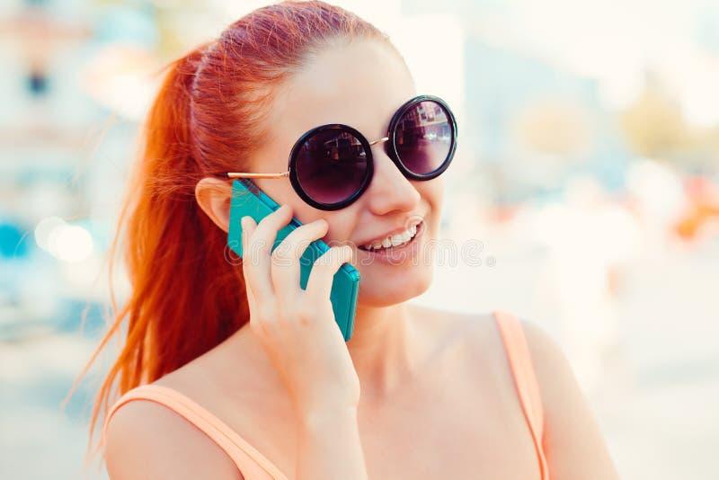 Gelukkige jonge vrouw die op mobiele telefoon spreekt stock foto's