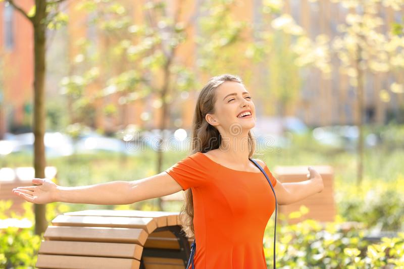 Gelukkige jonge vrouw die in park op zonnige dag rust royalty-vrije stock foto