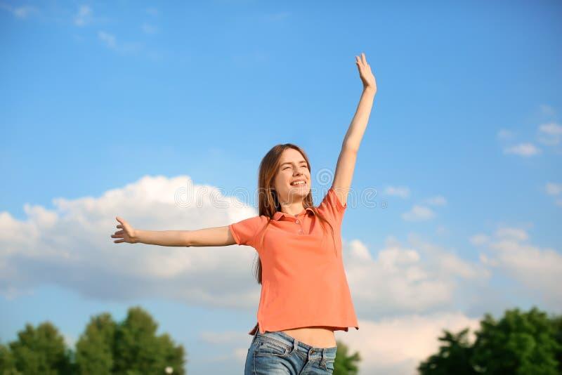 Gelukkige jonge vrouw die in park op zonnige dag rusten royalty-vrije stock foto's