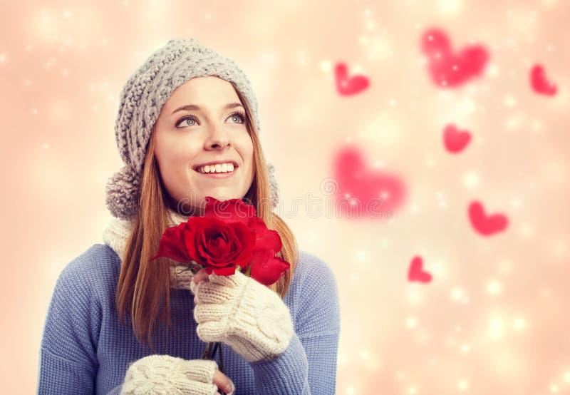 Gelukkige jonge vrouw die rode rozen houden royalty-vrije stock afbeeldingen