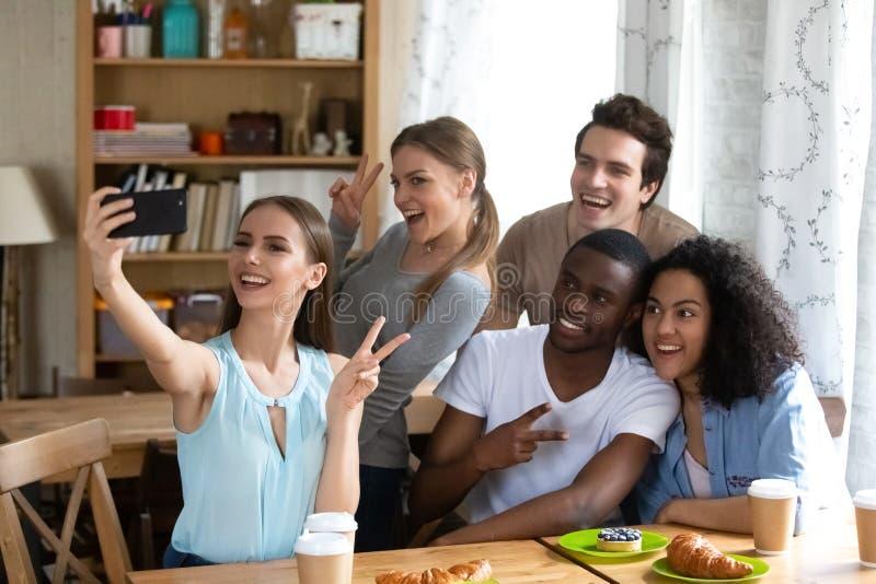 Gelukkige jonge vrouw die selfie met diverse vrienden maken stock foto