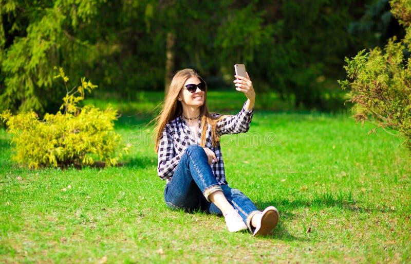 Gelukkige jonge vrouw die selfie neemt terwijl op gras in park zit royalty-vrije stock afbeelding