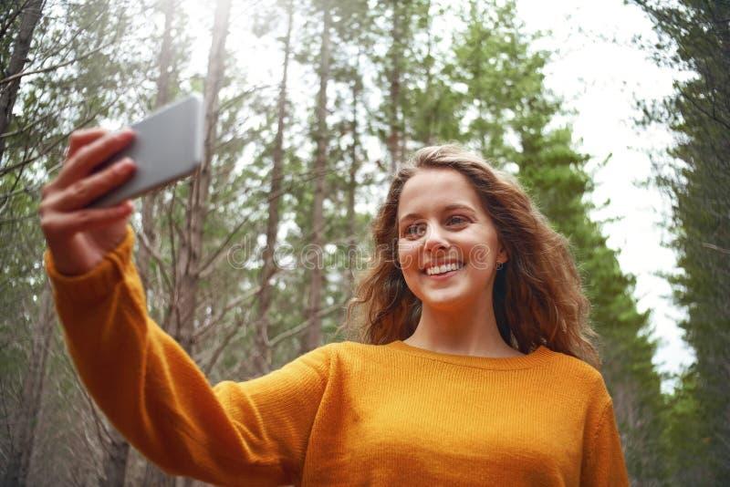 Gelukkige jonge vrouw die selfie op mobiele telefoon nemen stock afbeeldingen