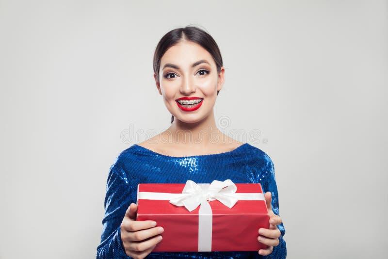 Gelukkige jonge vrouw die in steunen rode giftdoos met wit lint houden stock afbeelding