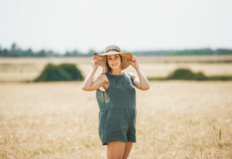 Gelukkige jonge vrouw die in strohoed van zon op tarwegebied genieten stock afbeeldingen