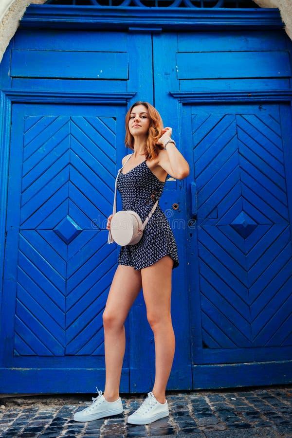 Gelukkige jonge vrouw die tegen blauwe houten deur glimlachen Openluchtportret van mooi tienermeisje die pret hebben stock foto
