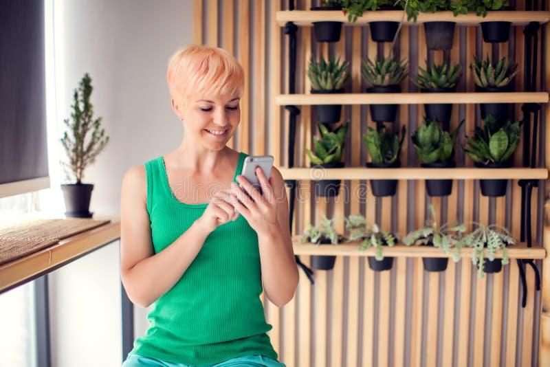 Gelukkige jonge vrouw die thuis het babbelen met haar touch screensmartphone ontspannen Mensen, technologieconcept royalty-vrije stock afbeeldingen
