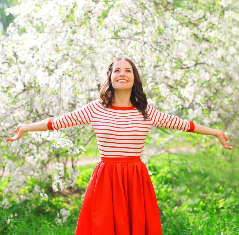 Gelukkige jonge vrouw die van geur in bloeiende de lentetuin genieten stock afbeeldingen