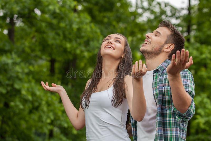 Gelukkige jonge vrouw die van regen in de zomer genieten stock foto
