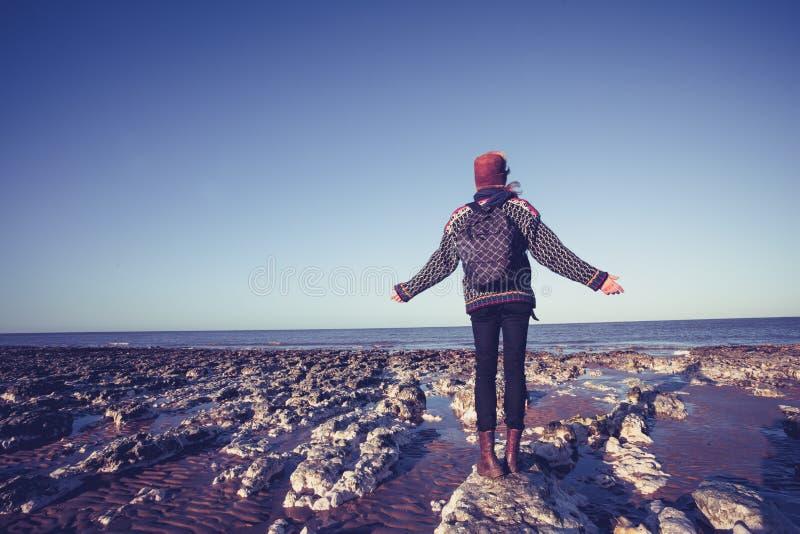 Gelukkige jonge vrouw die van rust van strand in de winter genieten stock fotografie