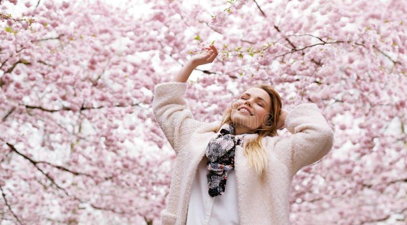 Gelukkige jonge vrouw die van verse lucht genieten bij het park van de de lentebloesem stock afbeeldingen