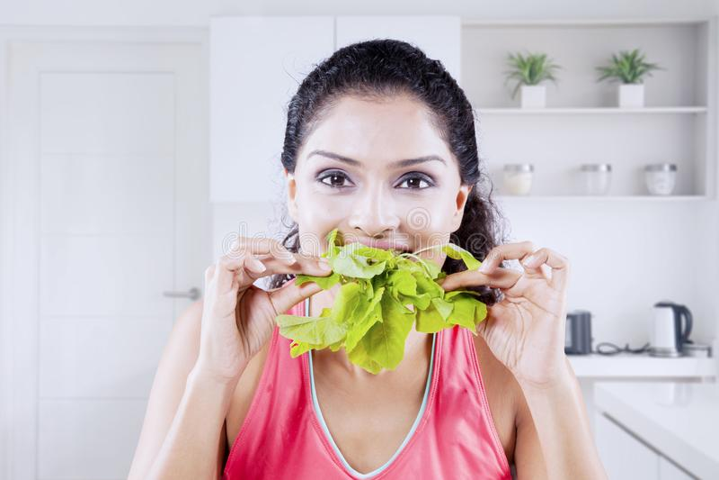 Gelukkige jonge vrouw die verse ruwe spinazie eten royalty-vrije stock fotografie