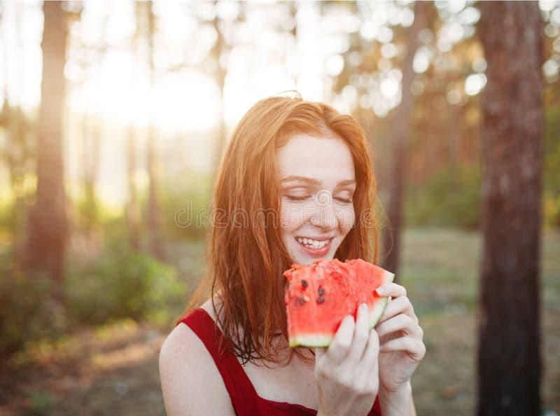 Gelukkige jonge vrouw die watermeloen op de aard eten de jeugdlevensstijl Geluk, vreugde, vakantie, strand, de zomerconcept royalty-vrije stock foto