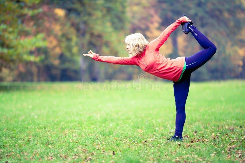 Gelukkige jonge vrouw die yoga in park doen stock foto