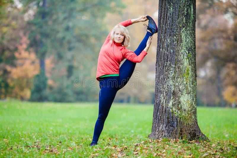 Gelukkige jonge vrouw die yoga in park doen stock fotografie