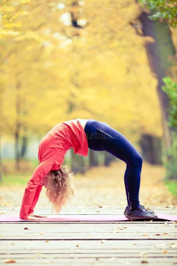 Gelukkige jonge vrouw die yoga in park doen stock foto's